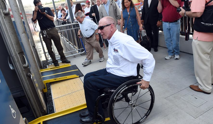 Billy Altom, of Little Rock, Arkansas, prepares to board a waiting train using a newly designed bridge plate that bridges the gap between the platform and the train during an event to celebrate the 25th Anniversary of the Americans with Disabilities Act at the Amtrak station in Ann Arbor, Mich., on Thursday, July 23, 2015. (Melanie Maxwell/The Ann Arbor News via AP)
