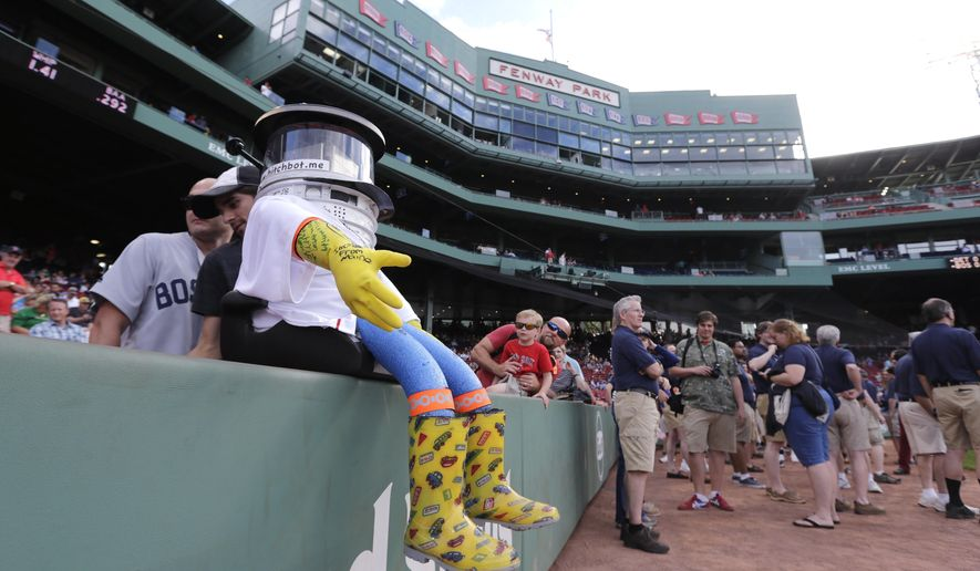 As pre-game activity begins, hitchBOT rests on the wall along the first base line before a baseball game at Fenway Park between the Boston Red Sox and Detroit Tigers in Boston, Friday, July 24, 2015. The robot's hitchhiking journey across the United States took a detour to Fenway. (AP Photo/Charles Krupa)
