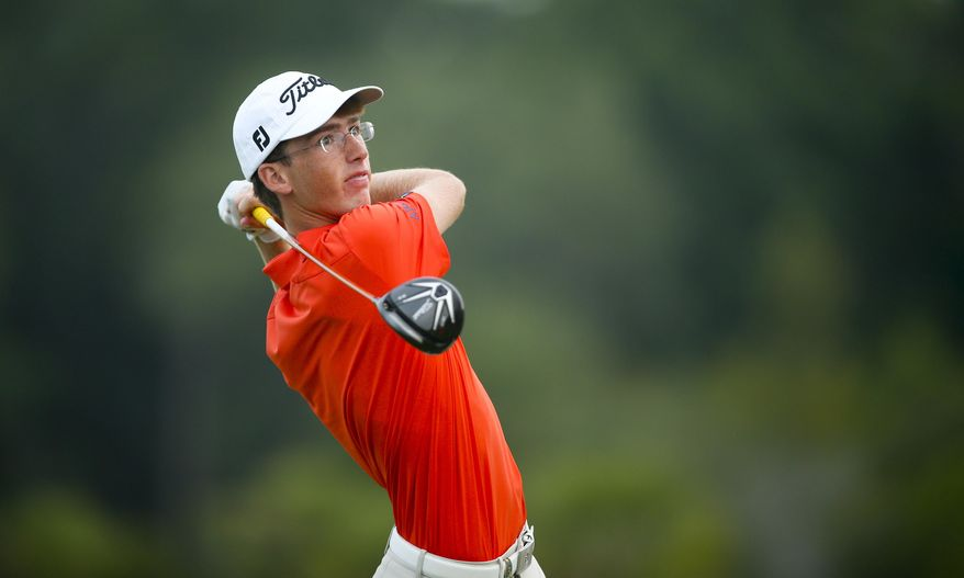 In this photo provided by the USGA, Andy Ogletree watches his tee shot on the 15th hole during the third round of match play of the 2015 U.S. Junior Amateur golf tournament at Colleton River Plantation Club in Bluffton, S.C. , on Friday, July 24, 2015. (Darren Carroll/USGA via AP)