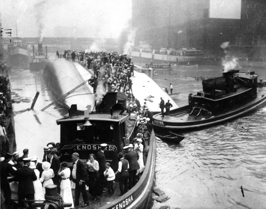 FILE - In this July 24, 1915 file photo, passengers are rescued as they stand atop The Eastland passenger ship after the vessel capsized in the Chicago River in downtown Chicago. As it was preparing to leave the dock, the Eastland rolled over, trapping passengers in the lower decks, where 844 drowned or were suffocated. On Friday, July 24, 2015 Chicago, historians and ancestors of the victims are marking the 100th anniversary of the disaster, the deadliest in city history. (AP Photo/File)