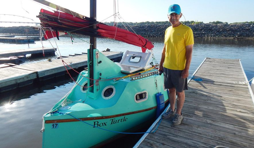 After pulling into the harbor the night before, Bert Chamberlain, of Moorhead, Minnesota, greeted a morning sunrise on Thursday, July 23, 2015 in Muscatine, Iowa. Chamberlain had dinner in Muscatine and also took a walk around downtown. His sailboat, which he built himself, is named the Box Turtle. Chamberlain, 64, began his journey down the mighty Mississippi on July 5 from Saint Paul, Minn.  (Ky Cochran/Muscatine Journal via AP)