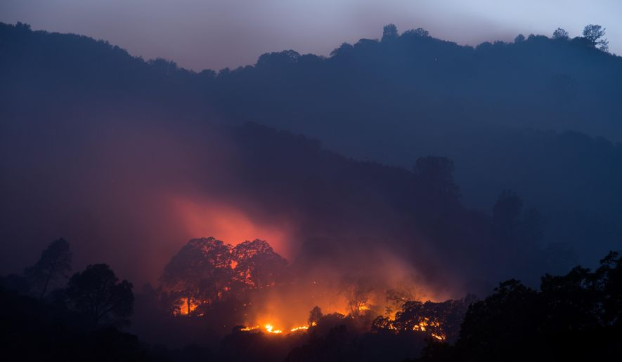 A backfire consumes vegetation as crews work to contain the Wragg fire near Winters, Calif., Thursday, July 23, 2015. According to Cal Fire, the blaze has scorched 6,900 acres and is 15 percent contained. (AP Photo/Noah Berger)