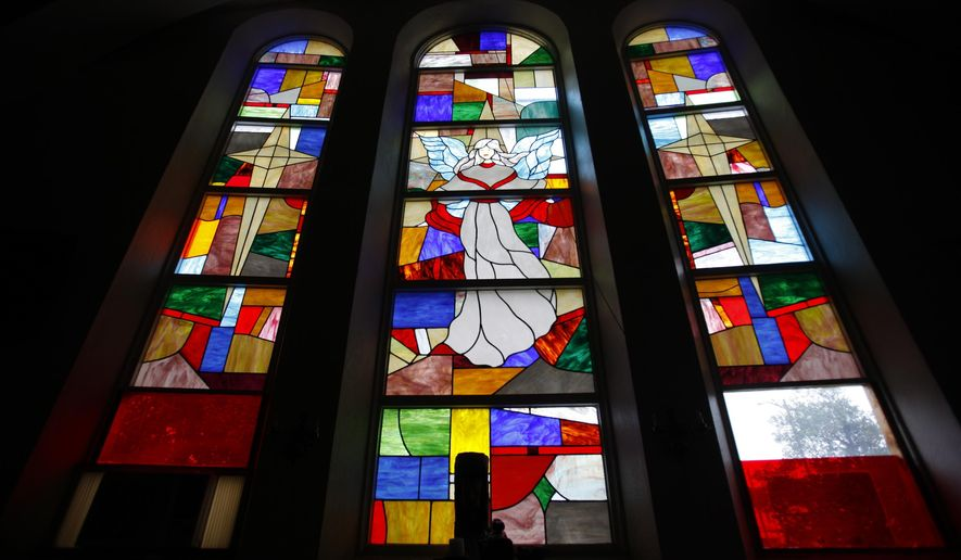 In a Wednesday, July 8. 2015 photo, sunlight illuminates the stained glass windows of Harvest International Full Gospel Church, created by stained glass artist Jerry A. William, on Washington Street in Petersburg, Va. For nearly four decades, churchgoers have worshipped under the bright streams of light, patterns and religious figures in stained glass handcrafted by local artist Williams. He has mostly designed windows for small rural churches across the state, and has a studio in his Halifax Street home. (Scott P. Yates/Progress-Index via AP)