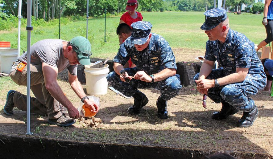 In this Monday June 15, 2015 photo provided by the US Navy, Dr. Martin Gallivan, left, an associate professor at the College of William and Mary, shows artifacts to Capt. Paul Haebler, commanding officer of Naval Weapons Station Yorktown, and Cmdr. Steven Fichter,  right, at Naval Weapons Station Yorktown. The field study is being conducted through the university as part of an ongoing cooperative agreement with Naval Facilities Engineering Command to survey historical sites aboard the installation. (Mark Piggott/U.S. Navy via AP)