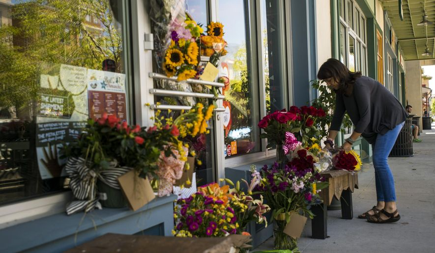 A woman leaves a bouquet of flowers at a makeshift memorial for store co-owner Jillian Johnson at Red Arrow Workshop in River Ranch in Lafayette, La., Friday, July 24, 2015. According to The Daily Advertiser, store co-owner Johnson was among the victims that died following the Thursday night shooting at the Grand 16 theater. (Paul Kieu/The Daily Advertiser via AP)