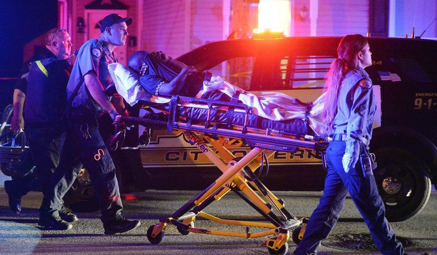 """A man on a stretcher is taken from the scene of a multiple shooting near the intersection of West 29th and Summit streets in Erie, Pa., on Saturday,  July 25, 2015. Erie police said a teenage was shot to death and at least six other people suffered gunshot wounds late Friday night in what authorities described as a """"shootout"""" near West 29th and Summit streets.(Andy Colwell/Erie Times-News via AP)  Mags Out; Mandatory Credit"""