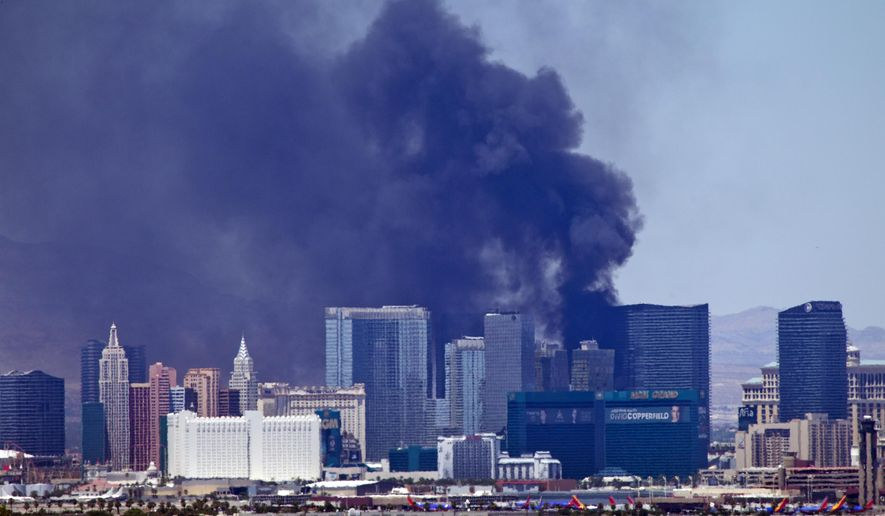 Smokes billows from a fire on the outside pool area of the Cosmopolitan Las Vegas hotel-casino in Las Vegas, Nevada Saturday, July 25, 2015. No injuries have been reported, and the cause of the fire has not been determined. Emergency vehicles were called to the resort shortly after noon. (Steve Marcus/Las Vegas Sun via AP)
