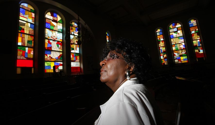ADVANCE FOR MONDAY JULY 27 AND THEREAFTER - In a Wednesday, July 8. 2015 photo, Chief Apostle Mary P. Bonner poses for a portrait as sunlight illuminates the stained glass windows of Harvest International Full Gospel Church stained glass artist Jerry A. Williams in Petersburg, Va. Williams crafted and installed the stained glass for the 117,307 square foot church about 20 years ago. Bonner, who heads the church, created the design; a patchwork of jewel-toned glass, from her own vision. (Scott P. Yates/Progress-Index via AP)