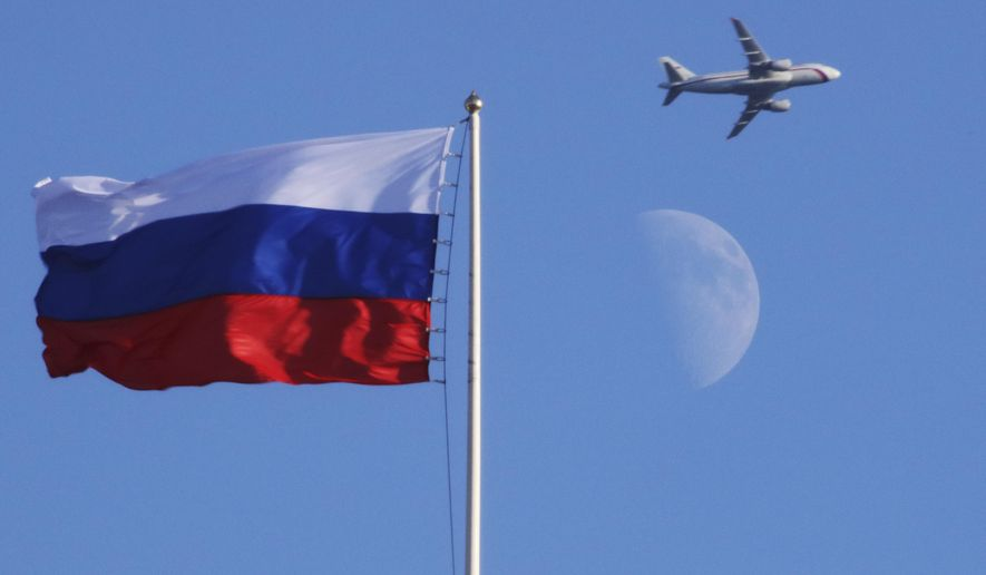 A plane flies over the Russian flag atop the Konstantin Palace in St.Petersburg, Russia, Friday, July 24, 2015. (AP Photo/Dmitry Lovetsky)