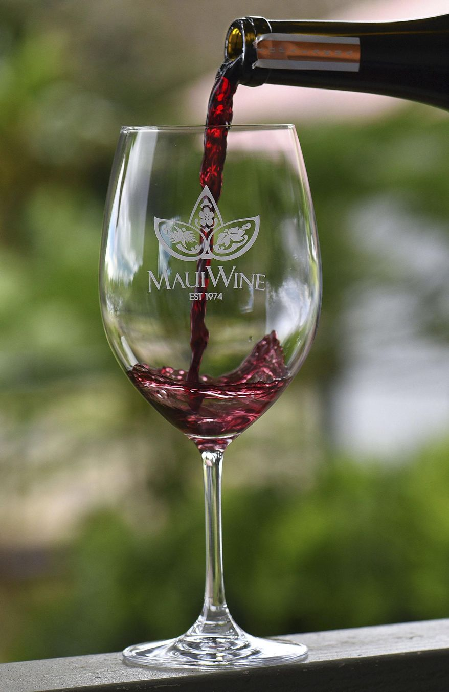 """ADVANCE FOR SATURDAY, JULY 25 - In this photo taken July 16, 2015, a glass of Syrah  is poured in the MauiWine tasting room in Kula, Hawaii. Longtime residents and visitors to the island have referred to Maui's only winery by different names. In 2000, Hegele decided to attach the tagline """"Maui's Winery"""" to some marketing and advertising pieces. In May, the transition to MauiWine began with an overhaul of the winery's website. (Matthew Thayer/ Maui News via AP)"""