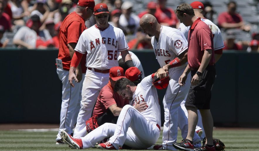 Los Angeles Angels left fielder Matt Joyce, bottom center, is examined by a team trainer as he is helped up by Albert Pujols, second from right, after colliding with Erick Aybar, not pictured, after they collided going for a fly ball hit by Texas Rangers' Delino DeShields, not pictured, during the fourth inning of a baseball game in Anaheim, Calif., Sunday, July 26, 2015. (AP Photo/Kelvin Kuo)