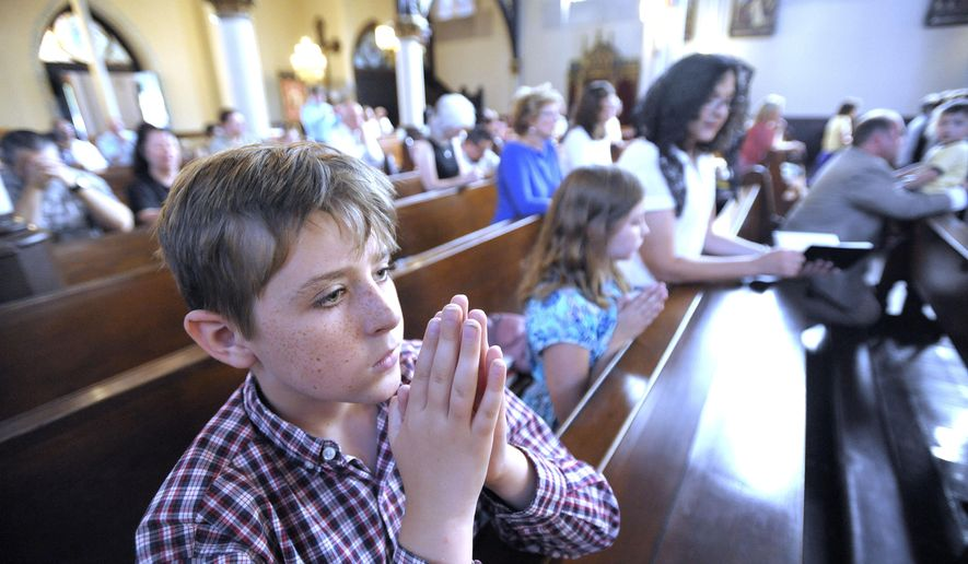 In this July 25, 2015, photo Thomas Carey, left, his sister Charlotte, center, and mother Anita, right, kneel as they pray during Mass at Saint Joseph Catholic Church in Detroit. The Detroit Mass Mob asked people to attend the service, which is in response to The Satanic Temple planning to unveil its controversial goat-headed Baphomet sculpture at an undisclosed location in Detroit. (Todd McInturf/Detroit News via AP)  DETROIT FREE PRESS OUT; HUFFINGTON POST OUT; MANDATORY CREDIT
