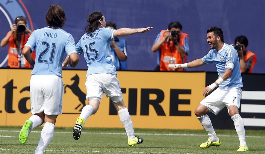 New York City FC's Thomas McNamara (15) celebrates his goal against Orlando City SC with teammate David Villa (7), of Spain, as Andrea Pirlo (21), of Italy, joins during the second half an MLS soccer game at Yankee Stadium, Sunday, July 26, 2015, in New York. New York defeated Orlando 5-3. (AP Photo/Jason DeCrow)