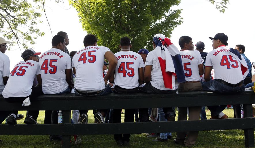 Pedro Martinez fans sit on a fence at the Clark Sports Center before the National Baseball Hall of Fame induction ceremony on Sunday, July 26, 2015, in Cooperstown, N.Y. Martinez , along with Former Major League Baseball players Randy Johnson, Craig Biggio and John Smoltz will be inducted to the National Baseball Hall of Fame on Sunday. (AP Photo/Mike Groll)