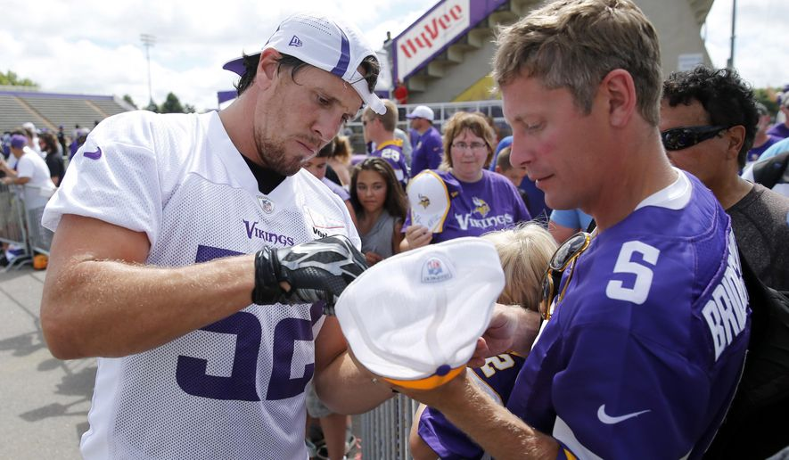 Minnesota Vikings outside linebacker Chad Greenway, left, signs autographs after a morning practice session at an NFL football training camp on the campus of Minnesota State University, Sunday, July 26, 2015, in Mankato, Minn. (AP Photo/Charles Rex Arbogast)