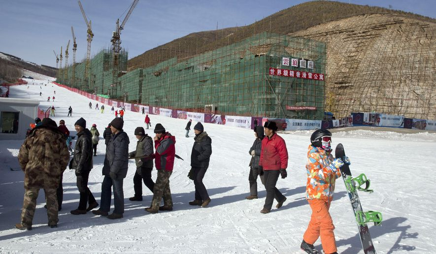 FOR STORY OLYMPICS 2022 BID - FILE - In this Saturday, Dec. 6, 2014 file photo, a snowboarder walks past migrant workers near a hotel under construction next to a ski slope at the Chongli ski resort in Hebei province where the Nordic skiing, ski jumping, and other outdoor Olympic events are proposed to be held for Beijing's 2022 bid. The International Olympic Committee will be faced with two starkly different choices, Beijing and Almaty in Kazakhstan , when it selects the host city for the 2022 Winter Games, on July 31 in Kuala Lumpur, Malaysia. (AP Photo/Ng Han Guan, File)