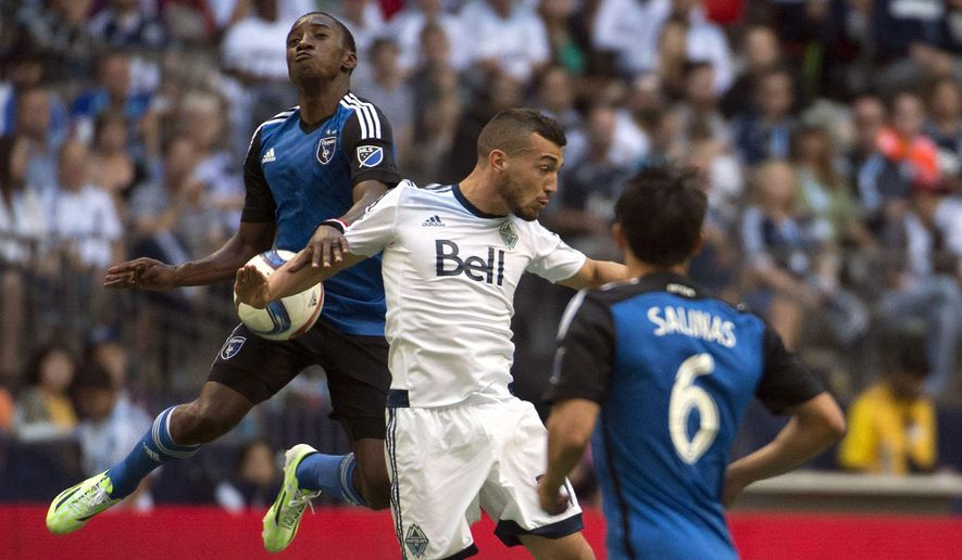 Vancouver Whitecaps FC Russell Teibert, centre, fights for control of the ball with San Jose Earthquakes Cordell Cato, left, and Shea Salinas, right, during the second half of MLS soccer action in Vancouver, British Columbia, on Sunday, July 26, 2015. (Jonathan Hayward/The Canadian Press via AP)