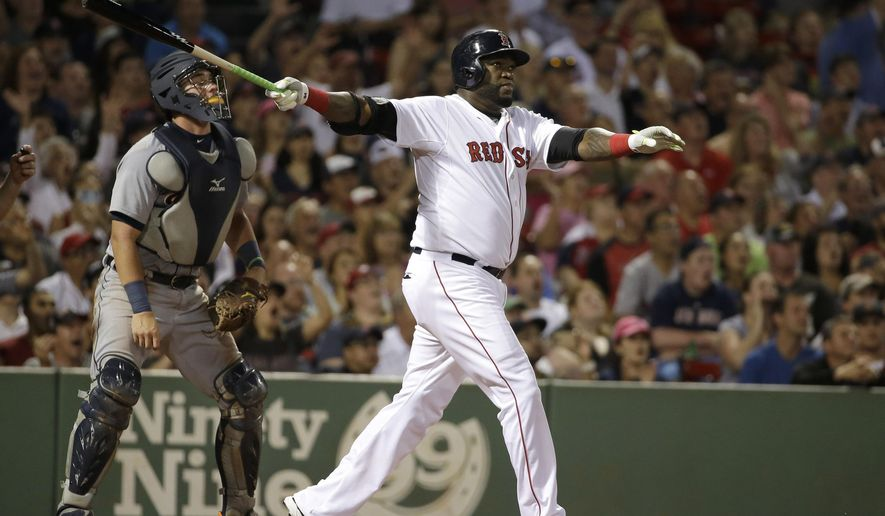 Boston Red Sox's David Ortiz, right, follows through on a three-run home run swing as Detroit Tigers catcher James McCann, left, looks on in the fifth inning of a baseball game Sunday, July 26, 2015, in Boston. (AP Photo/Steven Senne)