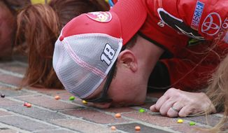Kyle Busch kisses the bricks on the start/finish line after winning the NASCAR Brickyard 400 auto race at Indianapolis Motor Speedway in Indianapolis, Sunday, July 26, 2015. (AP Photo/R Brent Smith)