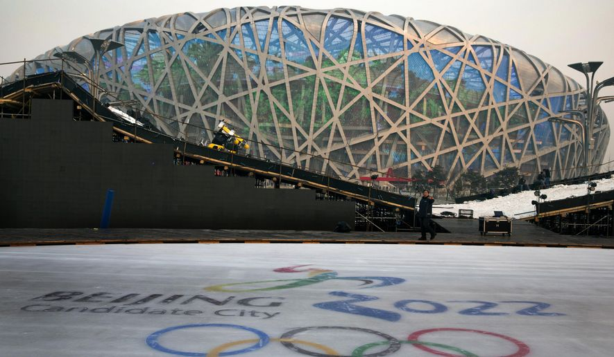 """FOR STORY OLYMPICS 2022 BID - FILE - In this Dec. 26, 2014 file photo, a worker walks past an ice rink with the logo for Beijing's Winter Olympics bid ahead of a countdown event to the new year in front of the iconic Beijing National Stadium """"Bird's Nest"""" in Beijing. The International Olympic Committee will be faced with two starkly different choices, Beijing and Almaty, Kazakhstan , when it selects the host city for the 2022 Winter Games, on July 31 in Kuala Lumpur, Malaysia. (AP Photo/Ng Han Guan, File)"""