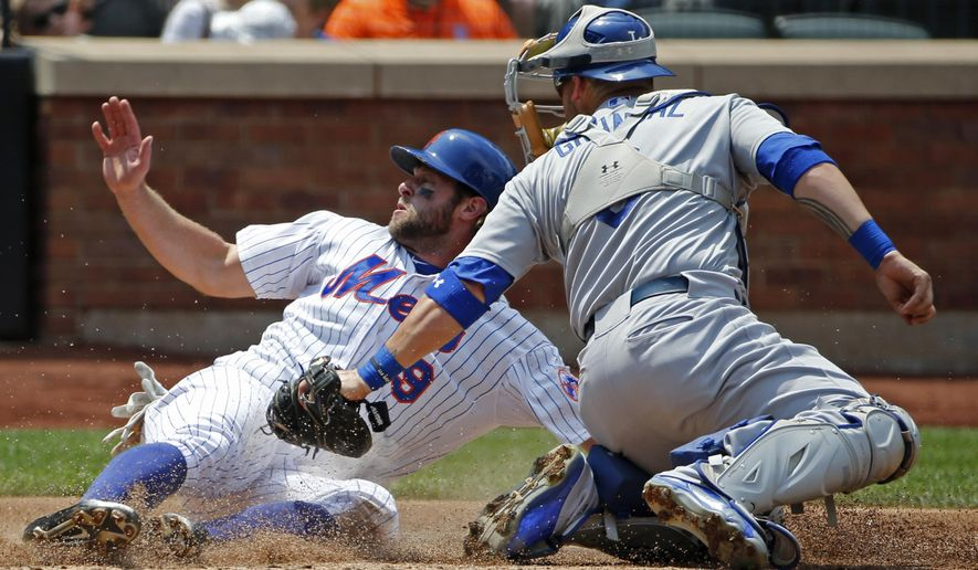 Los Angeles Dodgers catcher Yasmani Grandal, right, looks back for the call as New York Mets' Kirk Nieuwenhuis (9) scores on Jacob deGrom's third-inning RBI-single in a baseball game in New York, Sunday, July 26, 2015. (AP Photo/Kathy Willens)