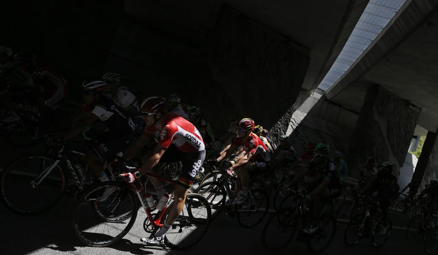 The pack passes through a tunnel during the twentieth stage of the Tour de France cycling race over 110.5 kilometers (68.7 miles) with start in Modane and finish in Alpe d'Huez, France, Saturday, July 25, 2015. (AP Photo/Laurent Cipriani)