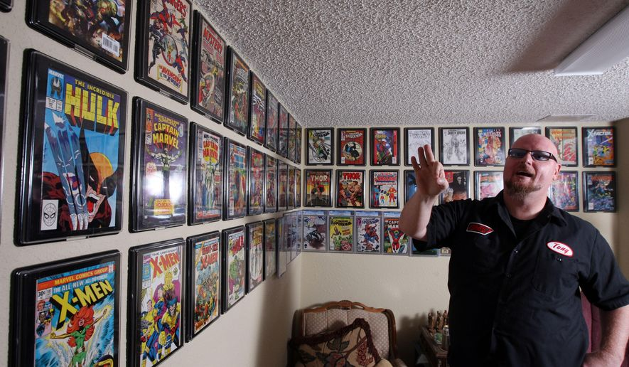 FOR RELEASE SUNDAY JULY 26, 2015 AT 12:01 A.M. CDT -Tony Onesto tslks about some of the special comic books in his collection of 70,000 Tuesday July 7, 2015 at his home in Burlington, Iowa. He has a few special ones on his wall that were given to him and or signed by the authors and artists. The passion started in his childhood and was re ignited with the urging of his wife, Jacqueline, the past couple years. (John Gaines/The Hawk Eye via AP)