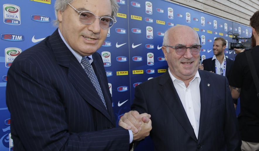 Carlo Tavecchio, president of the Soccer Italian Federation, right, shakes hand with Maurizio Beretta, president of the Serie A league federation prior to the draws for the upcoming Italian soccer Serie A championship in Rho, near Milan, Italy, Monday, July 27 , 2015. The season 2015/16 will start on Aug. 22.  (AP Photo/Luca Bruno)