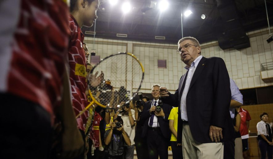 Thomas Bach, right, president of the International Olympic Committee (IOC) speaks to the members of a Malaysian badminton youth team at a badminton training center in Kuala Lumpur, Malaysia, Monday, July 27, 2015. Malaysia will host the 128th International Olympic Committee executive board meeting this week where the vote for the host cities of the 2022 Olympic Winter Games and for the 2020 Youth Olympic Winter Games will take place. (AP Photo/Joshua Paul)