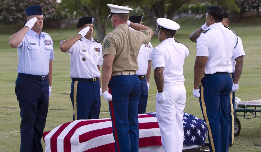 Military pallbearer salute the exhumed remains of unidentified crew members of the USS Oklahoma killed in the 1941 bombing of Pearl Harbor that were disinterred from a gravesite at the National Memorial Cemetery of the Pacific, Monday, July 27, 2015 in Honolulu.  The cemetery and the Defense POW/MIA Accounting Agency plan to disinter 61 caskets to identify the remains.  (AP Photo/Marco Garcia)