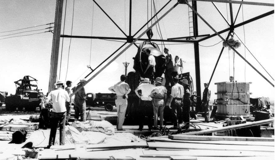 """FILE - In this July 1945, file photo, scientists and workmen rig the world's first atomic bomb to raise it up into a 100-foot tower at the Trinity bomb test site in the desert near Alamagordo, N.M. """"The Bomb,"""" which begins airing Tuesday, July 28, 2015, on most PBS stations, seeks to tell the story of the deadly device as the 70th anniversary of the atomic bombings of Hiroshima and Nagasaki approaches. (AP Photo/File)"""