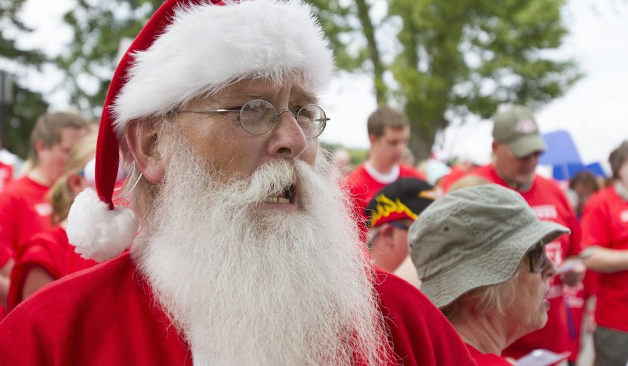 "Rick Maynard, of Clinton Township, Mich.,sings during an attempt to break the Guinness World Record for most people caroling at once at St. Lorenz Church in Frankenmuth, Mich. Saturday, July 25, 2015. Maynard is a professional Santa. St. Lorenz Church and School said Monday there were about 500 fewer people than needed at Saturday's ""Christmas in July"" event. (David C. Bristow/The Saginaw News via AP) ALL LOCAL TELEVISION OUT; LOCAL TELEVISION INTERNET OUT; MANDATORY CREDIT"