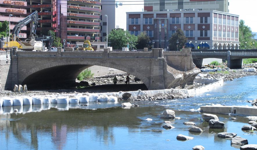 In this June 23, 2015 photo, demolition crews work in downtown Reno, Nev., on the historic Virginia Street Bridge that since has been completely removed with a new bridge expected to open in May 2016. Unexpected discoveries during the demolition process, including some contaminated soil and the granite foundation of a previous bridge built in 1877, have boosted the cost of the project by about $410,000. (AP Photo/Scott Sonner)