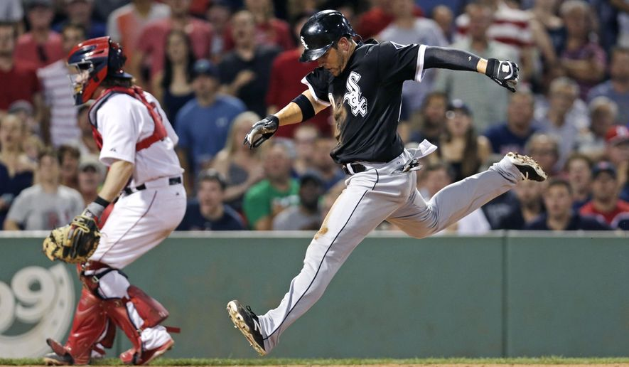 Chicago White Sox's J.B. Shuck scores on a single by teammate Tyler Flowers, as Boston Red Sox catcher Ryan Hanigan, left, looks for the ball during the seventh inning of a baseball game at Fenway Park in Boston, Monday, July 27, 2015. (AP Photo/Charles Krupa)