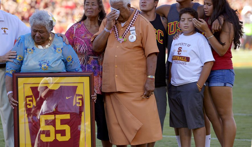 FILE- In this Sept. 1, 2012, file photo, family members of Junior Seau including his mother Luisa Seau, far left, and his father Tiaina Seau, third from left, stand during a ceremony to honor the former Southern California player during the first half of an NCAA college football game between Hawaii and Southern California in Los Angeles. The family of the late Junior Seau will not disrupt the Hall of Fame ceremonies on Aug. 8, 2015, despite their disagreement with a policy preventing live remarks during a posthumous induction. (AP Photo/Mark J. Terrill, File)