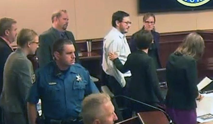 In this image taken from Colorado Judicial Department video, James Holmes, top fourth from right in light-colored shirt, gets a pat on the arm from a member of his defense team following testimony from Holmes' younger sister Chris, during the penalty phase of Holmes' trial, Monday, July 27, 2015, in Centennial, Colo. (Colorado Judicial Department via AP, Pool)