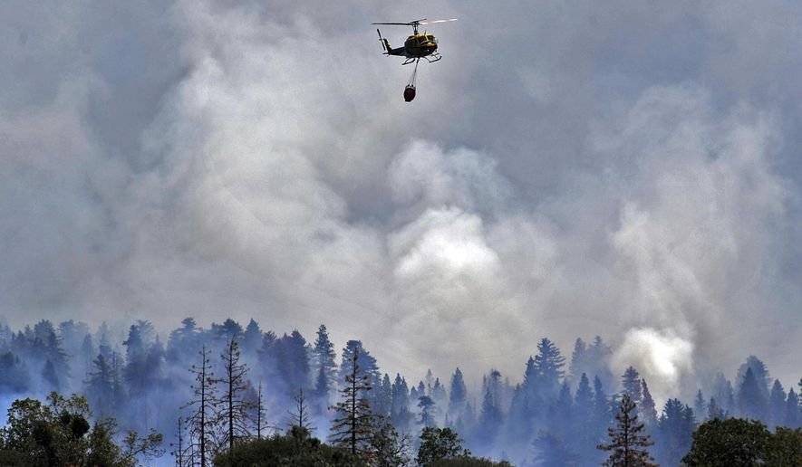 A helicopter flies away from a burning ridge after dropping water on the Willow Fire near Bass Lake, Calif., Monday, July 27, 2015. (Eric Paul Zamora/The Fresno Bee via AP)