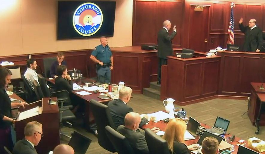 In this image taken from Colorado Judicial Department video, Colorado theater shooter James Holmes, top second from left in light-colored shirt, sits in court, as Judge Carlos A. Samour Jr., far right, swears in witness Dr. Jeffrey Metzner, who gave testimony during the penalty phase of Holmes' trial, Monday, July 27, 2015, in Centennial, Colo. Metzner, the court-appointed psychiatrist who concluded that James Holmes was legally sane when he attacked a Colorado movie theater, says Holmes' mental illness still is what caused him to kill 12 people and injure 70 others. (Colorado Judicial Department via AP, Pool)