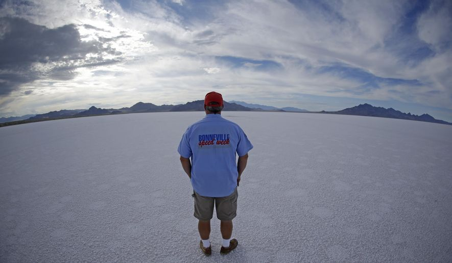 In this Monday, July 20, 2015 photo, Bill Lattin, the Southern California Timing Association president and Speed Week race director, stands in the Bonneville Salt Flats in Utah. A small city of tents, trailers and thousands of visitors appears almost every August in the Utah desert to watch cars, motorcycles and anything with wheels rocket across gleaming white sheets of salt at speeds of 400 mph. But wet weather has forced the cancellation of Speed Week for the second straight year and revived a debate about whether nearby mining is depleting the Bonneville Salt Flats of their precious resource. (AP Photo/Rick Bowmer)