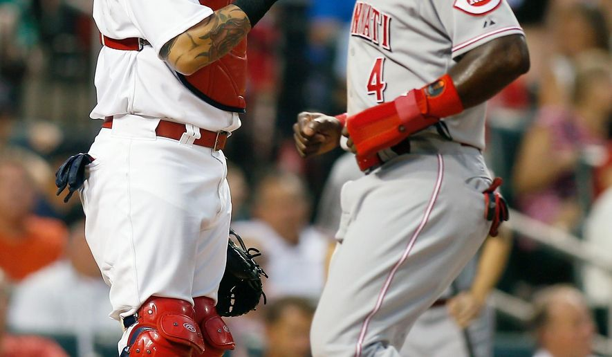 St. Louis Cardinals catcher Yadier Molina, left, looks on as Cincinnati Reds' Brandon Phillips scores on a sacrifice fly by Jay Bruce during the third inning of a baseball game against the St. Louis Cardinals, Monday, July 27, 2015, in St. Louis. (AP Photo/Scott Kane)