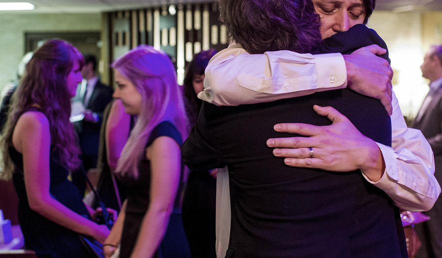 "Jason Brown, husband of Jillian Johnson, hugs a guest following the funeral service for Jillian Johnson at Delhomme Funeral Home in Lafayette, La., Monday, July 27, 2015. Johnson was a victim of the The Grand 16 movie theater shooting in Lafayette on Thursday. Johnson, 33, and Mayci Breaux, 21, were shot and killed last Thursday while watching the movie ""Trainwreck"" at The Grand 16 movie theater in Lafayette, leaving stunned friends and family questioning how two lives off to such promising starts could end so tragically. (Paul Kieu/The Daily Advertiser via AP, Pool)"