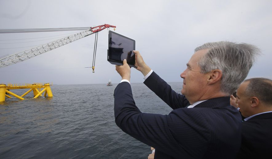 Sen. Sheldon Whitehouse, D-R.I., photographs the first foundation jacket installed by Deepwater Wind in the nation's first offshore wind farm construction project Monday, July 27, 2015, on the waters of the Atlantic Ocean off Block Island, R.I. Deepwater Wind will consist of five turbines producing a total of 30 megawatts of electricity. (AP Photo/Stephan Savoia)