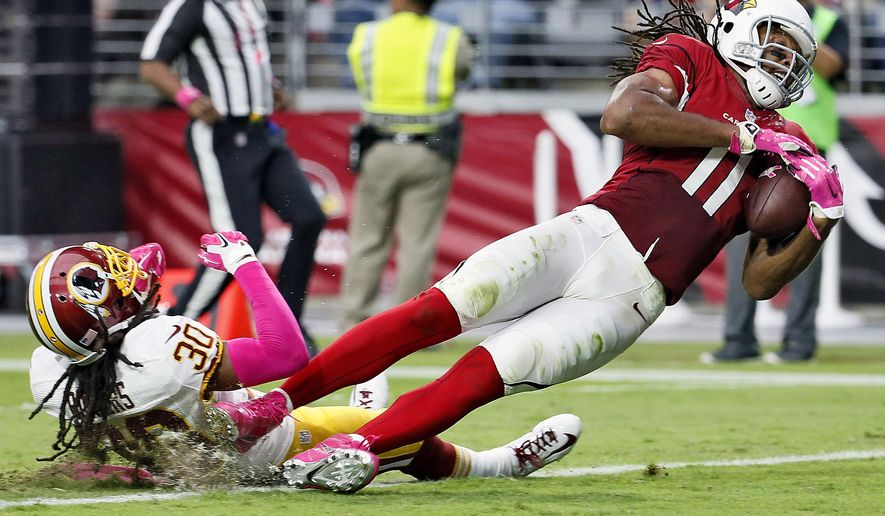 FILE - In this Oct. 12, 2014, file photo, Arizona Cardinals wide receiver Larry Fitzgerald (11) falls into the end zone for a touchdown as Washington Redskins free safety E.J. Biggers (30) defends during the first half of an NFL football game in Glendale, Ariz. (AP Photo/Matt York, File)