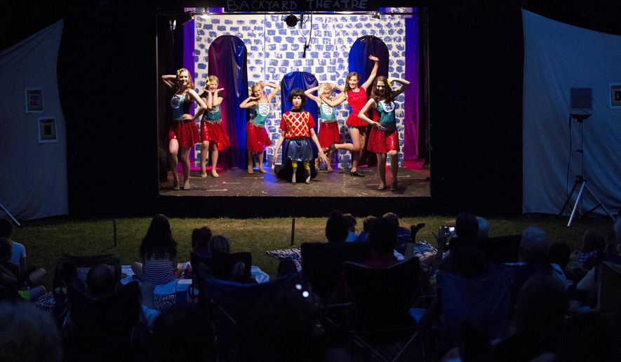 """In a July 24, 2015 photo, Director Dylan Lawrence center, playing Lord Farquaad in """"Shrek: The Musical"""" performs on the opening night in Lincoln, Neb. Dylan, 13, along with a group of neighborhood kids referred to as the Backyard Theater Company, came together to produce, choreograph, design, direct, and perform the play for family and friends for the second year in a row.  (Jenna Vonhofe/Lincoln Journal Star via AP)"""