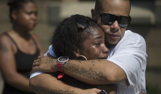 Mourners Shanicca Soloman cries in the embrace of friend Terrell Whitney outside funeral services for Samuel Dubose at the Church of the Living God in the Avondale neighborhood of Cincinnati, Tuesday, July 28, 2015. Dubose was fatally shot by a University of Cincinnati police officer who stopped him for a missing license plate. (AP Photo/John Minchillo)