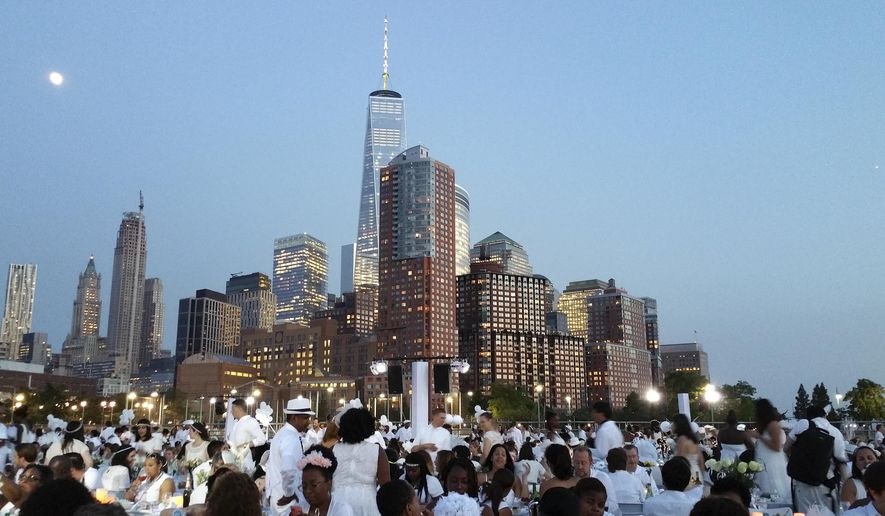 People dressed in white have dinner on Pier 26 along the Hudson River during the Diner en Blanc event, Tuesday, July 28, 2015, in New York. Thousands of people attended the world's largest popup picnic, at a location revealed at the last moment. (AP Photo/Verena Dobnik)