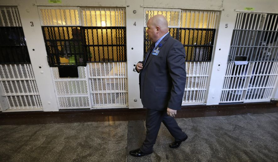 FILE - In this Nov. 18, 2013 photo, warden Nick Ludwick walks past a row of cells at the Iowa State Penitentiary in Fort Madison, Iowa. Inmates are still facing tight security measures that were imposed on July 5, 2015 after Justin Kestner, a dangerous felon, escaped. Kestner was captured several hours later in Illinois. (AP Photo/Charlie Neibergall)