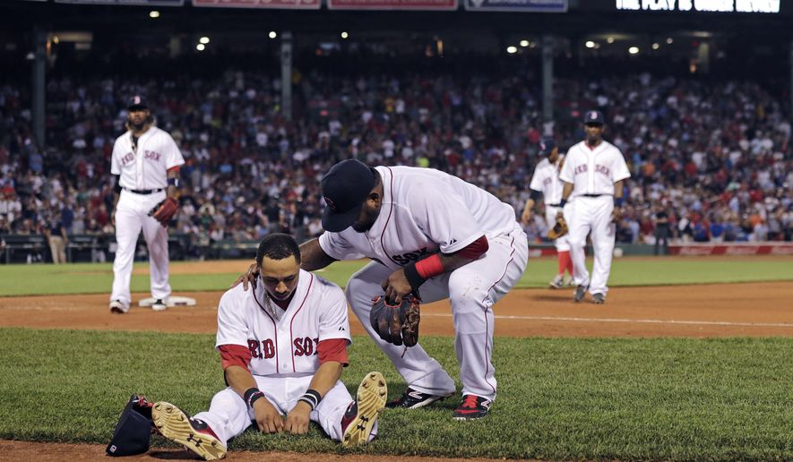 Boston Red Sox center fielder Mookie Betts sits on the infield as teammate Pablo Sandoval checks to see if he's injured following a play where Betts flipped over the bullpen wall while trying to catch a drive by Chicago White Sox's Jose Abreu during the sixth inning of a baseball game at Fenway Park in Boston, Tuesday, July 28, 2015.  Betts left the game after the play. (AP Photo/Charles Krupa)