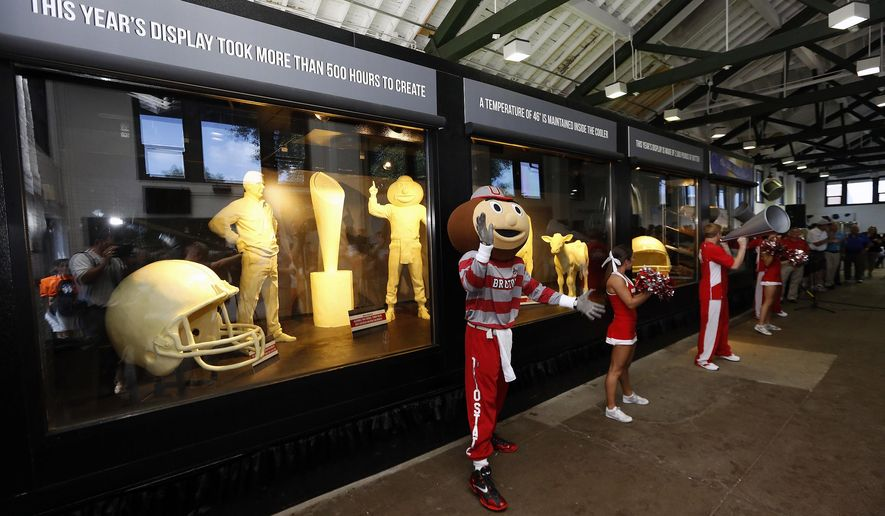 Ohio State Buckeyes mascot Brutus claps his hands after the unveiling of the Ohio State fair butter cow and Ohio State football display in the dairy building at the Ohio State fairgrounds, Tuesday, July 28, 2015, in Columbus, Ohio. Ohio State football sculptures are joining the traditional butter cow and calf in a 46-degree cooler in the American Dairy Association display. Also displayed is a butter sculpture depicting Ohio State NCAA football coach Urban Meyer, second from left in back. (Kyle Robertson/The Columbus Dispatch via AP)