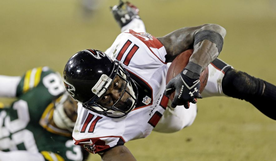 FILE - In this Dec. 8, 2014, file photo, Atlanta Falcons' Julio Jones is tripped up by Green Bay Packers' Tramon Williams after a catch during an NFL football game in Green Bay, Wis. Jones, who set career highs with 104 catches for 1,593 yards last year, is entering the final year of his contract. (AP Photo/Tom Lynn, File)
